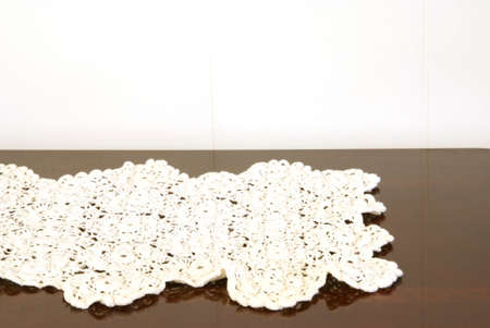 polished: Antique crocheted doily on polished cherry wood table. Stock Photo