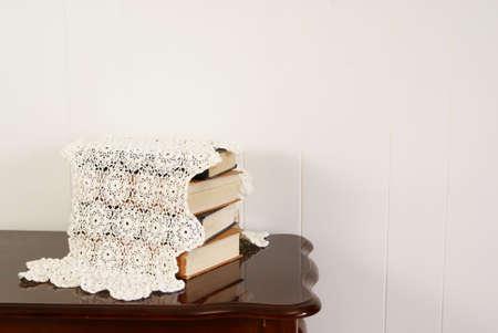 家の飾る本とダークウッド桜テーブル上ドイリー。