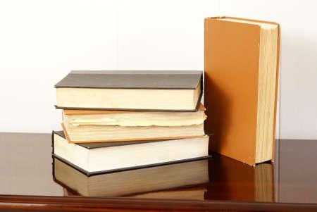Old hardback books on polished dark cherry wood table