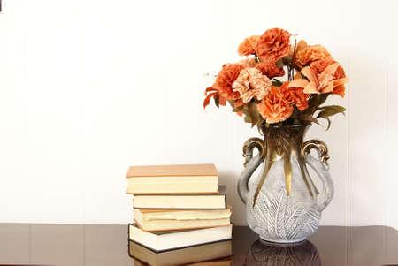 絹の花瓶の花の古いハードカバー本のスタックの横にあります。