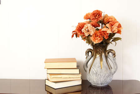 hardback: Vase of silk flowers next to stack of old hardback books.