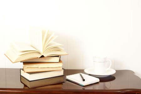仕事や勉強します。本は磨かれた暗いチェリーの木のテーブル cofee、ペンとメモ帳上に積層されました。
