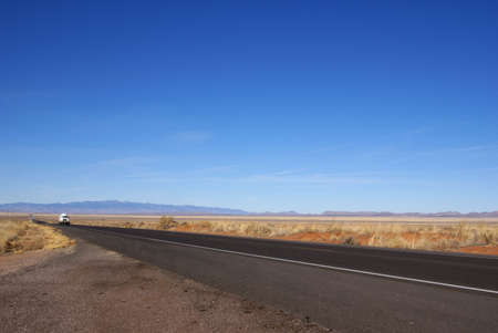wide open spaces: Lone truck travels Central New Mexico USA road with wide open spaces around and mountains in the far distance. Stock Photo