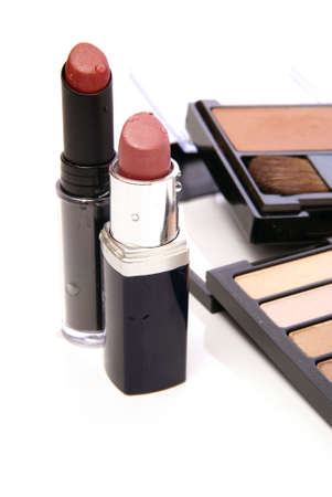 Two moist lipsticks on white with blurred makeup in the background