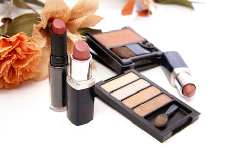 Makeup cosmetics with peach colored lily and carnation flowers on white. photo