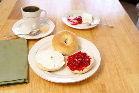 bagel: Breakfast of plain bagels with coffee, cream cheese, and strawberry preserves.