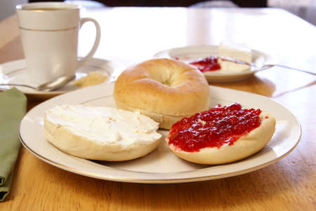 Breakfast of plain bagels with coffee, cream cheese, and strawberry preserves.
