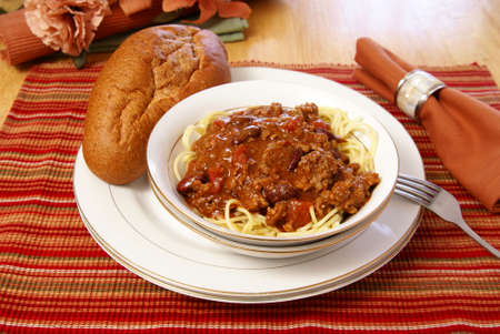 Western style meat and bean chili served on top of spaghetti with a side of rustic wheat bread.