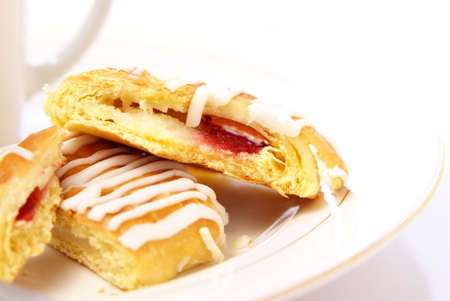 Danish pastry with strawberry and cream cheese filling, on plate next to cup of cappuccino. High key, low depth. Stock Photo