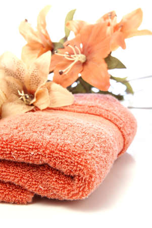 Spa, beauty, or home decor concept. Fluffy burnt orange towel accented by silk flowers on white.