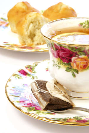 Beautiful cup of tea with spoon and teabag on matching saucer, and hint of cake muffins in the background