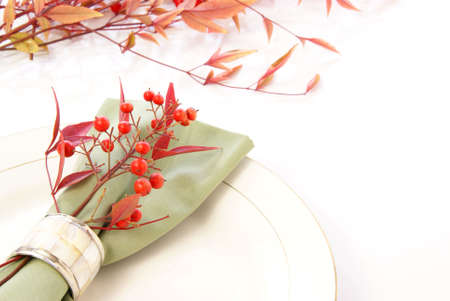napkin ring: Beautiful green napkin table decor with napkin ring, red leaves, and berries on white plates.