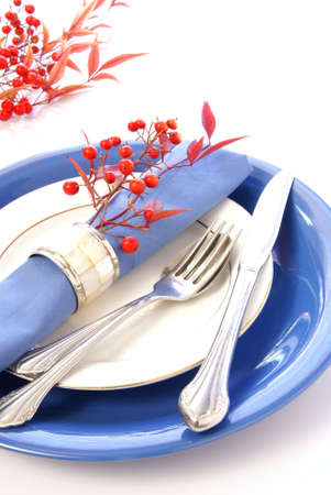 Elegant table setting in blue and white, with fresh sprigs of leaves and berries photo