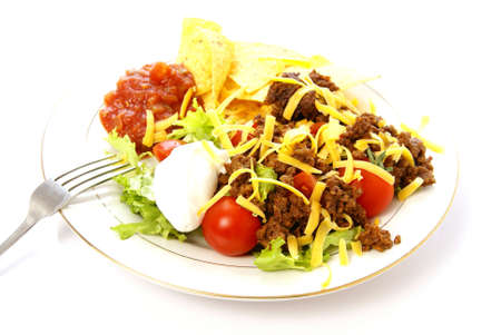 Taco salad with seasoned ground beef, lettuce, tomato, cheese, sour cream, salsa, and corn chips