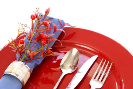Elegant table setting in red and blue, with fresh sprigs of leaves and berries