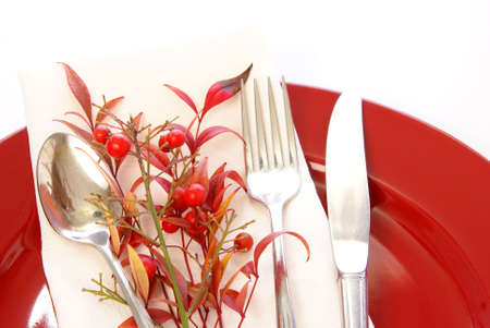 Elegant table setting in red and white, with fresh sprigs of leaves and berries