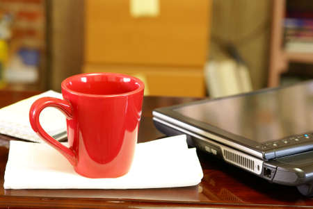 Empty coffee cup sitting next to a tablet pc computer on wood desk in home office. Stock Photo - 2753299