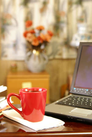 Cup of coffee on desk next to laptop computer in small home office Stock Photo - 2753274