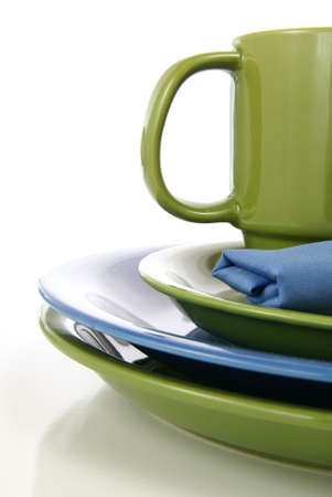 Green and blue tableware setting with plates, coffee mug, and cloth napkin.
