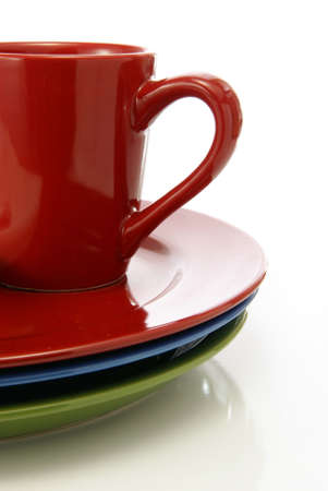 Red coffee mug sitting on matching colorful dinner plates.