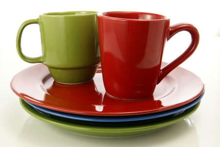 Red and green coffee mugs sitting on matching colorful dinner plates.
