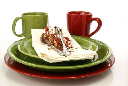 Green and red tableware setting with plates, coffee mugs, and cloth napkin.