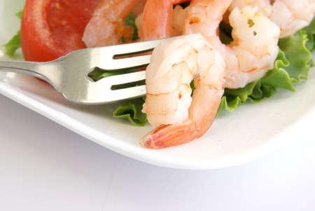 Shrimp on a fork with shrimp salad in the background. photo