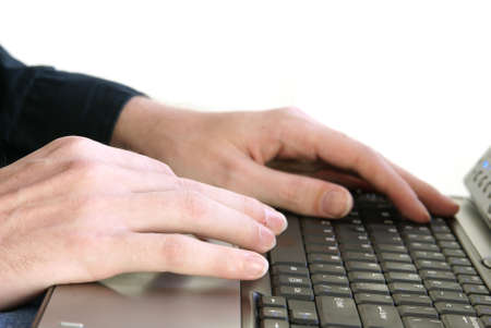 Male hands with long thin fingers on laptop keyboard.