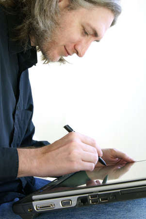 Man with digital stylus writing on slate style Tablet PC computer screen. Focus on hand with stylus. Stock Photo