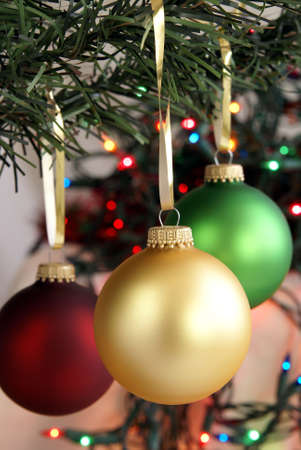 Christmas ornaments hanging from the tree with gold ribbon