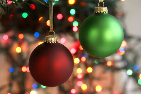 Frosted green and red Christmas ornaments hanging in front of blurred Christmas lights