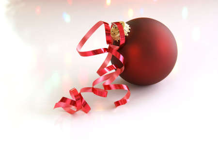 Red Christmas tree ball with curled red ribbon and tree lights reflecting off the background