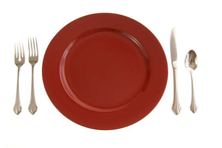 Table setting with red plate and silverware on white Imagens