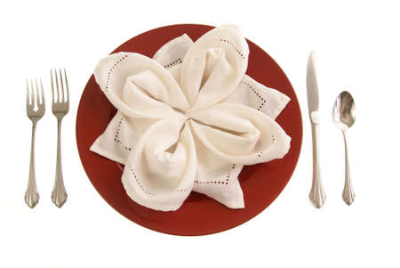 Elegant table setting. Red plate with cloth napkin folded in petal fashion