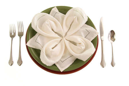 Elegant table setting with green and red plates, a petal folded cloth napkin, and silverware on white