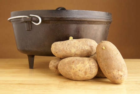 Rustic cooking concept with cast iron pan and raw potatoes on wood block table