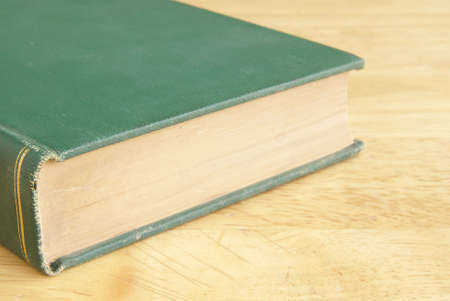 Vintage hardback book with green cover laying on a yellow wooden table