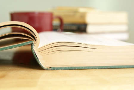 Libro de tapa dura de edad, por la que se abrirá en una mesa con libros y borrosa taza de café en el fondo Foto de archivo - 4949199