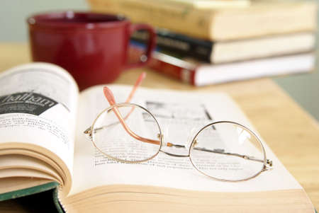 Eyeglasses on open book with coffee and other books stacked in the background. Stock Photo