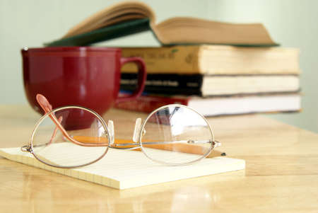 Eyeglasses on a yellow notepad with books and coffee behind