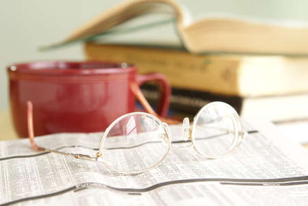 Eyeglasses on newspaper financial pages with books and coffee in the background