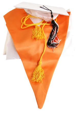 Honors Graduation Still life.White graduation gown and cap, orange honors stole, gold honors cord with tassles, and a graduation cap tassel on white