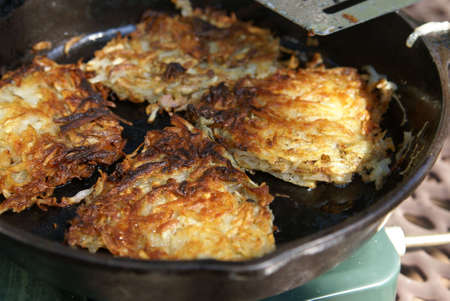 browns: Home made shredded potato hash browns cooking in a cast iron skillet