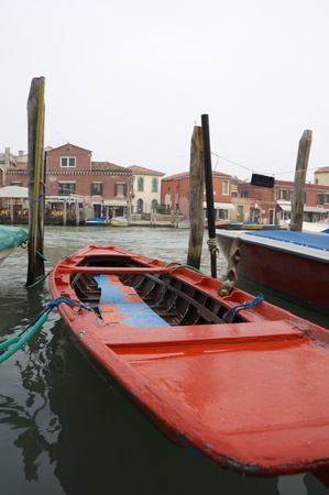 Wide angle close-up, taken with tripod extended on the water, of boat moored on a canal in Murano island, Venice, Italy. Selective focus and shallow depth of field. Autumn cloudy day. photo