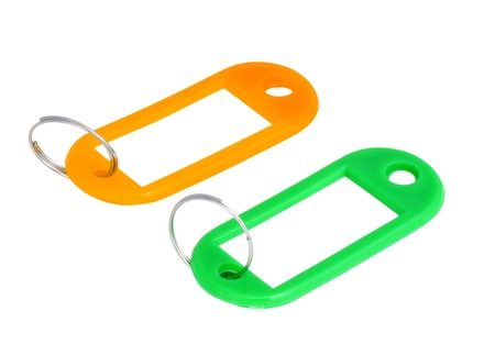 keylock: Two key tags with labels, one orange, one green, isolated on white, no shadows.