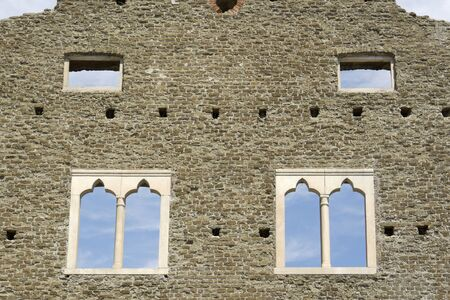 effectively: Castrum Caetani was built on the ancient Appian Way (Appia Antica) in the 14th century, next to Cecilia Metella Mausoleum, effectively including it. Here you can see a detail of its facade, with windows, against a summer bright day sky. Stock Photo