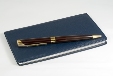chequera: Primer plano de una pluma que se reclina sobre un talonario de cheques (cheques). Estudio aislado en blanco, con algunas sombras. Foto de archivo