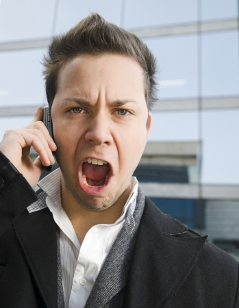 Young upset man shouting on mobile phone outside contemporary office building. photo
