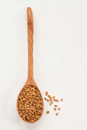 fenugreek in a wooden spoon on a white background Zdjęcie Seryjne