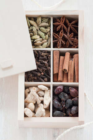 set of spices in a box on a wooden background